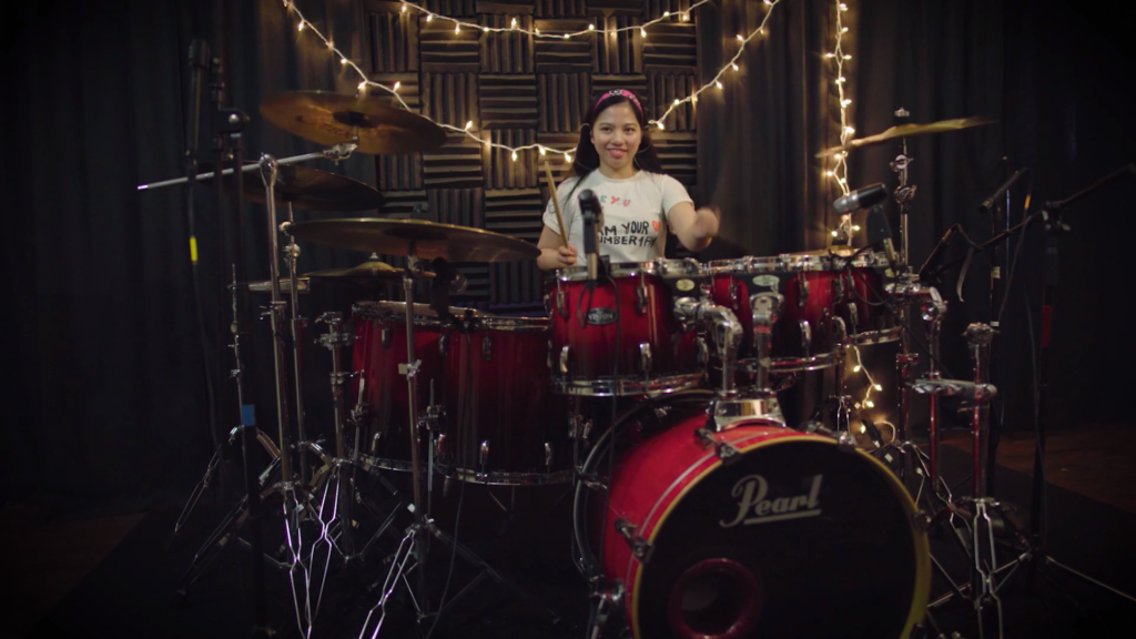 girl in a studio playing the drums