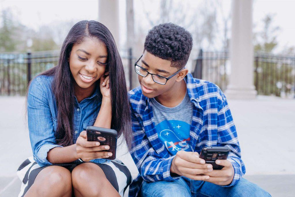 two siblings looking at phone
